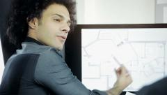 Modern cool architect showing project on computer to client Stock Footage