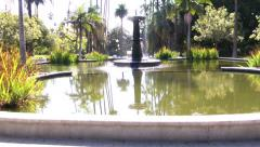 Couple walking and sitting down to fountain Stock Footage
