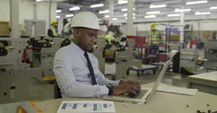 African American manager working on his laptop in a factory. Stock Footage