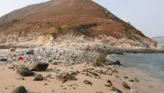 Rocky beach tail near the island hill. Camera rotates right Stock Footage