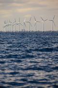 Wind turbines power generator farm along coast sea Kuvituskuvat