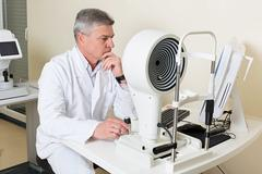 Ophthalmologist sitting near the equipment Stock Photos