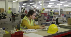 A female manager on a laptop in a busy production factory. Stock Footage