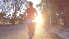 Young Female Running on Road at Sunset. Slow Motion Stock Footage