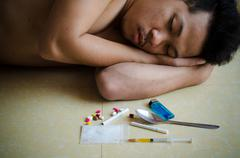 drug addict laying on floor - stock photo