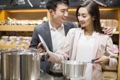 Young couple buying cooking utensil in supermarket Stock Photos