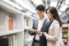 Stock Photo of Young couple choosing books in bookstore