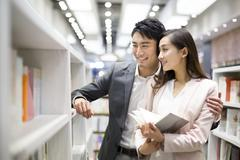 Young couple choosing books in bookstore Stock Photos