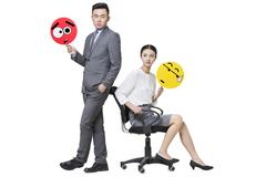 Business person holding embarrassed emoticon faces - stock photo