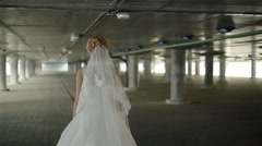 A young bride in a white wandering alone about the parking. Middle shot - stock footage
