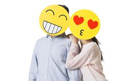 Young couple with cartoon emoticon faces in front of their faces Stock Photos