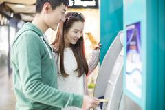 Young couple using ATM Stock Photos