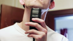 Man shaving electric razor in the bathroom Stock Footage