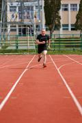 Healthy man run on athletics race sport track and representing concept of spo Stock Photos