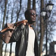 Fashion portrait of handsome african man in black leather jacket with bag out - stock photo