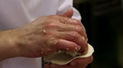 Chef hand preparing dough with rolling pin for asian food on wooden board at Stock Footage
