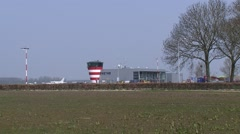 Skyline Lelystad Airport terminal, main building, small plane landing + pan Stock Footage