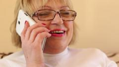 Senior woman with white smartphone speaks and gesticulate Stock Footage