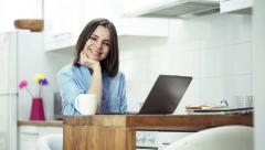 Portrait of happy woman with laptop sitting by table in kitchen  HD Stock Footage