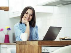 Portrait of happy woman with laptop sitting by table in kitchen  NTSC Stock Footage