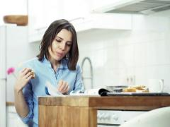 Young woman reading newspaper and eating bread in kitchen at home NTSC Stock Footage