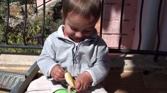 Toddler examines a banana Stock Footage