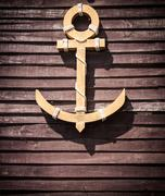 yellow wooden anchor on wooden wall background in retro style - stock photo