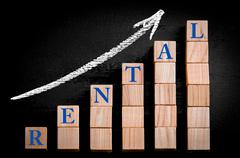 Word RENTAL on ascending arrow above bar graph of Wooden small cubes  - stock photo
