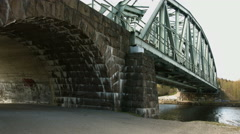 Bicyclist passes under a modern railbridge Stock Footage