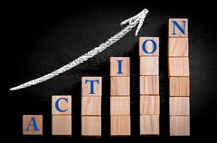 Word ACTION on ascending arrow above bar graph of Wooden small cubes - stock photo