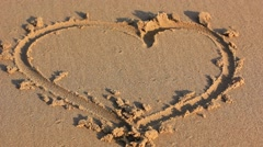 Love heart on sand washed away by wave Stock Footage