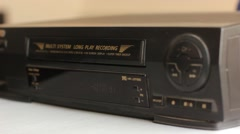 Inserting the video cassette into the VCR Stock Footage