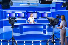 television newscaster and teleoperator at TV studio - stock photo