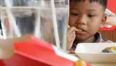 Young boy eating french fries, fast food restaurant background. 60 fps. Stock Footage