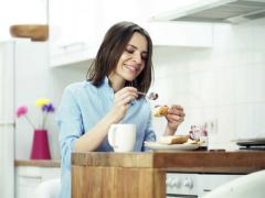 Woman preparing sandwich, eating and drinking coffee by table in kitc NTSC Stock Footage