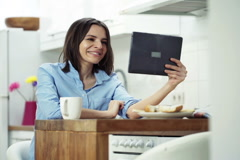 Young woman chatting on tablet computer sitting by table in kitchen at home NTSC - stock footage