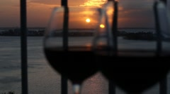 Two glasses with red wine on balcony  at sunset, focus on sun Stock Footage