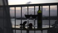 Two glasses and bottle with red wine on balcony with blowing curtains  at sunset Stock Footage