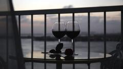 Two glasses with red wine on balcony with blowing curtains at sunset Stock Footage