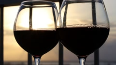 Two glasses with red wine on balcony  at sunset Stock Footage