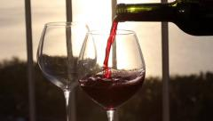 Pouring red wine in to glasses on balcony  at sunset Stock Footage