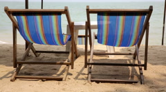 Two blue deck chairs on beach with blue sea Stock Footage
