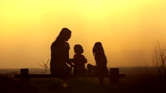 Silhouette of mum and children in sunset Stock Footage