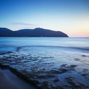 Stock Photo of Baratti bay, headland hill, rocks and sea on sunset. Tuscany, Italy.