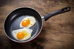 frying eggs in pan on table - stock photo