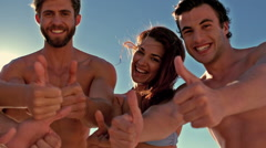 Attractive friends looking at camera thumbs up Stock Footage
