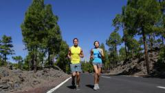 Young Fit Couple Running and Jogging on Road Stock Footage