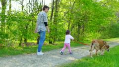 Family Life With Happy Mother And Child Walking Dog Outdoor - stock footage