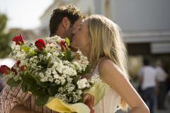 A man giving a woman flowers Stock Photos