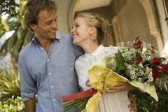 A couple with a rose bouquet outdoors Stock Photos